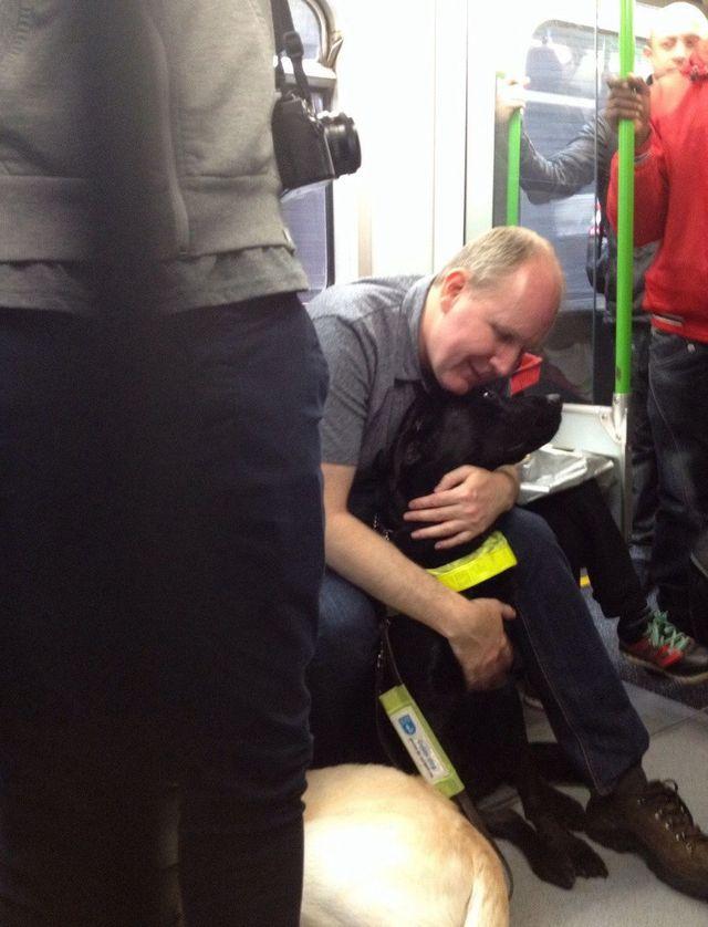 15. Слепой мужчина обнимает свою собаку-поводыря.
