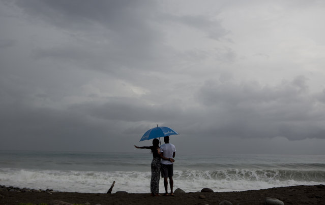 A couple watches the sea under the rain in Kingston, Jamaica, Sunday, October 2, 2016. (Photo by Edu