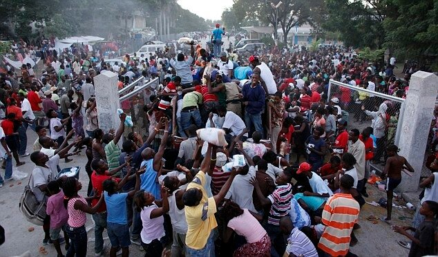 Анархия на Гаити People climb up a food distribution truck in Port-au-Prince