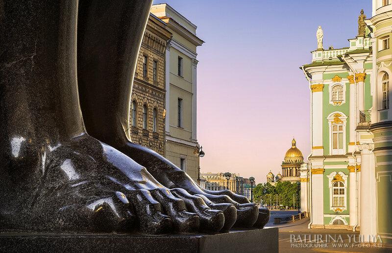 Огромные пальцы атланта на фоне города Huge thumbs of an atlant and city view