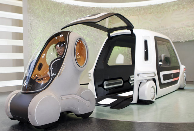 """Suzuki's one-person electric vehicle """"Pixy"""" comes out of the """"SSC"""" (Suzuki Sharing Coach) at a"""