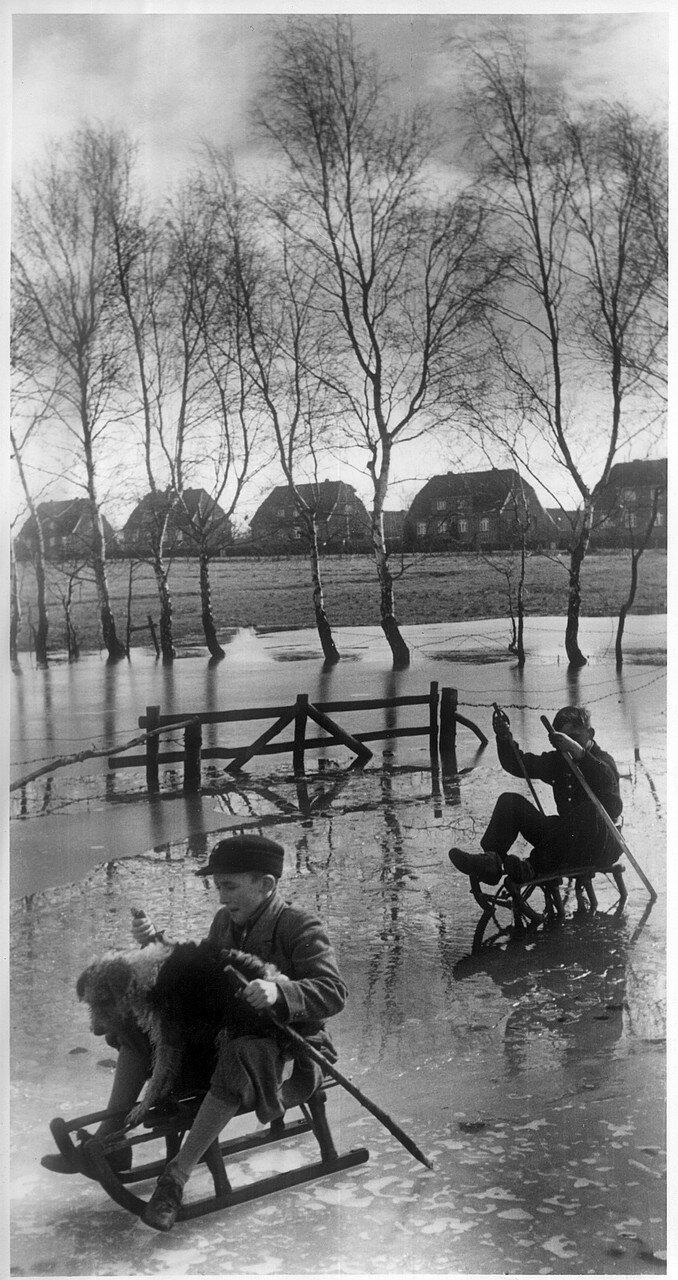 Гамбург. Дети зимой катаются на санках на замерзшем ручье Тарпенбек