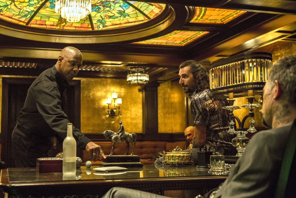 McCall (DENZEL WASHINGTON, left) discusses Teri with Slavi (DAVID MEUNIER, right) and Tevi (ALEX VEADOV, center) while the others watch in Columbia Pictures' THE EQUALIZER.