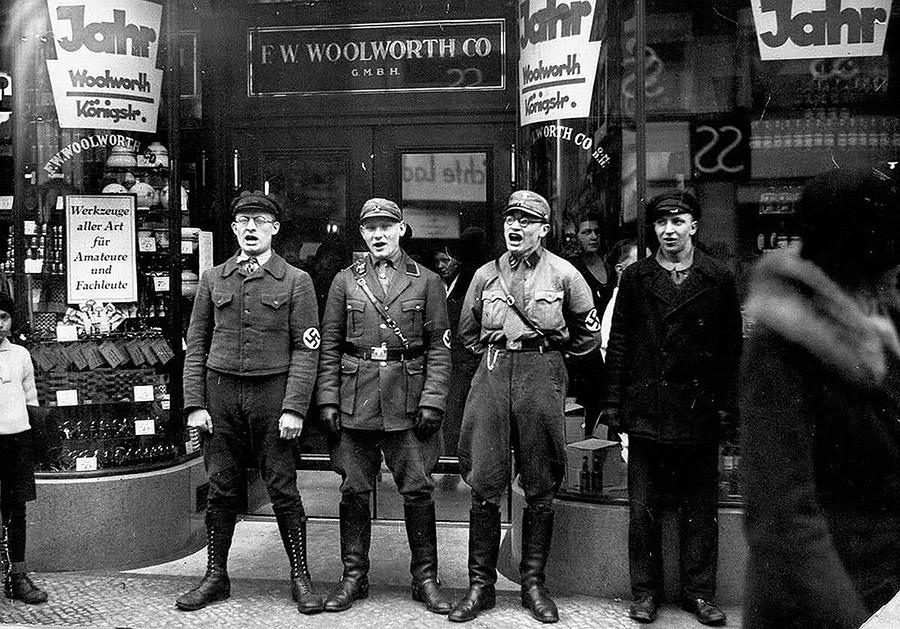 Нацисты поют у еврейских магазинов живописи, чтобы побудить немцев выступить за закрытие магазинов.