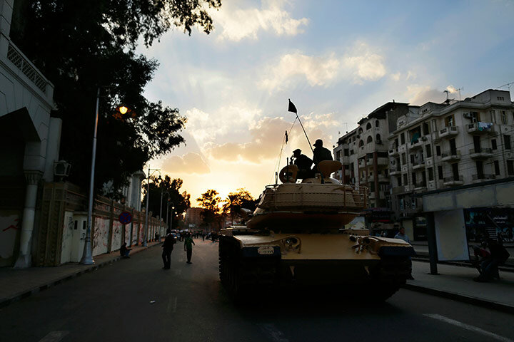 Egyptian army soldiers sit on top of their tank as the sun sets in the city