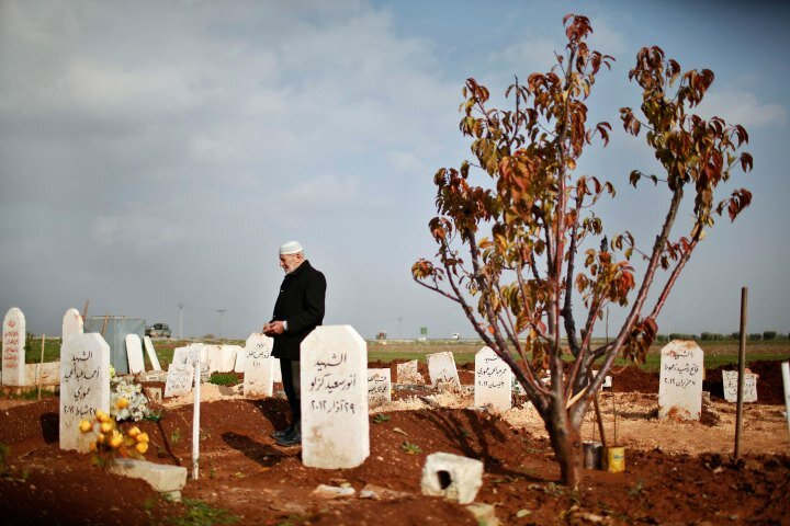 Abdlhamid Haj Omar, 70, a father who lost three sons and two grandsons in the ongoing Syrian crisis, prays as he visits their graves at the Martyrs' cemetery in Azaz city, North Aleppo
