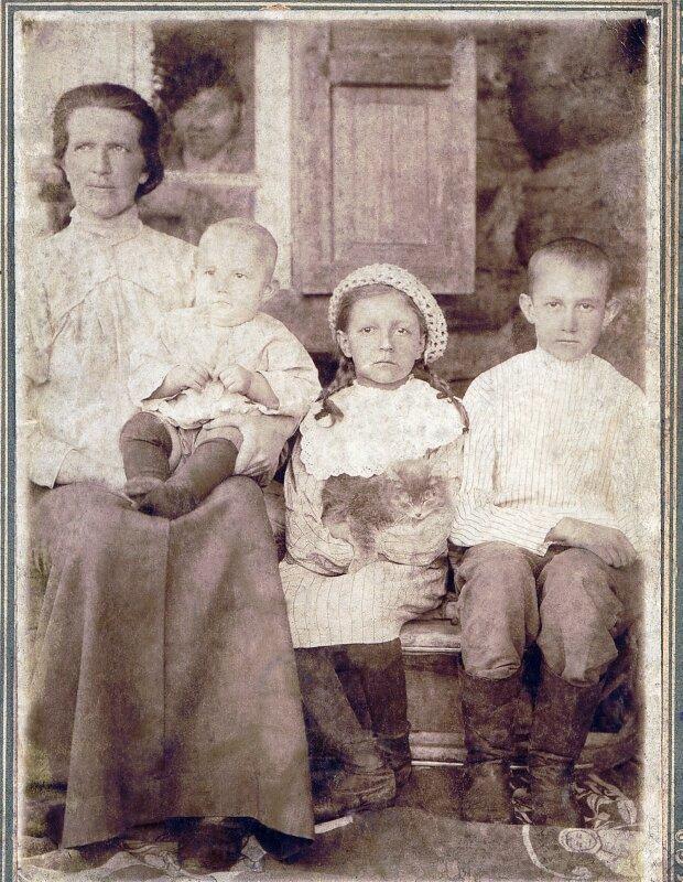 На руках у мамы, предположительно,- дочь Вера,сидят рядом Лида и Виталий.