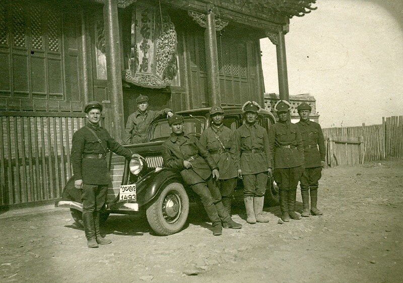 Soldiers of the Red Army and the Mongolian Peoples' Army posing together beside an automobile, Mongolia, 1938-39.