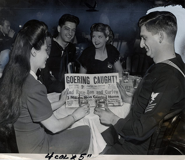 Perusing a late edition of the Journal-American, couples celebrate the new 4 AM curfew hours that went into effect for enlisted men at the end of World War II