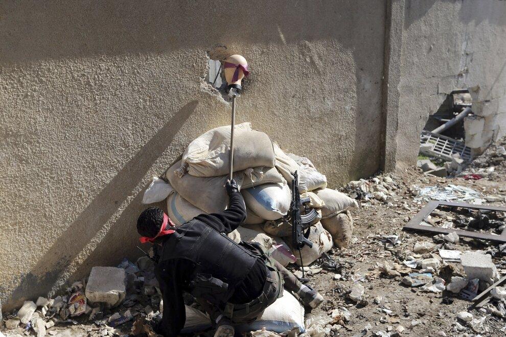 Боец, так называемой Свободной сирийской армии, пытается выманить снайпера во время столкновения с регулярными войсками в пригороде Дамаска