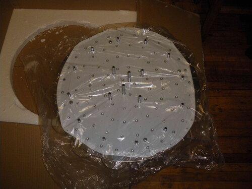 Фото 3. Извлечение люстры с дистанционным управлением из коробки. На лицевую поверхность люстры приклеена защитная плёнка.