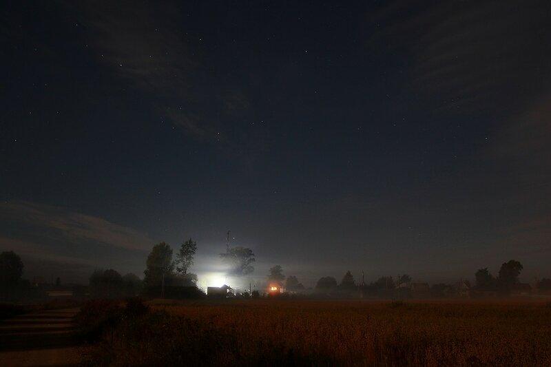 Языки тумана, звёздное небо, огни деревни Жданухино и лунные тени на дороге рядом с полем