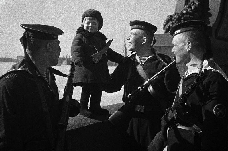 Моряки Балтийского флота с маленькой девочкой Люсей, родители которой умерли в блокаду. Ленинград, 1943.