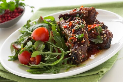 Pork ribs in ginger glaze with salad.