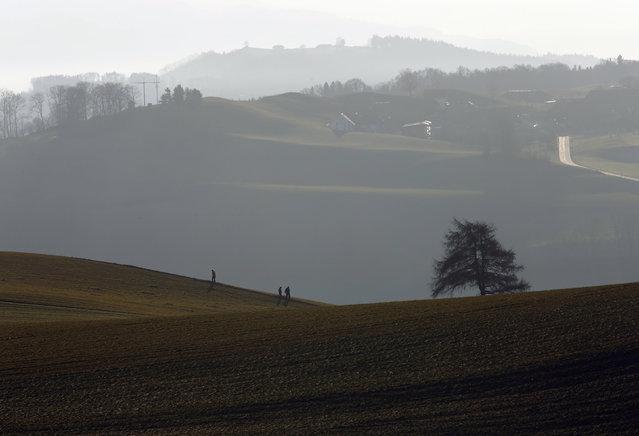 Poeple walk on a field on the Gurten mountain in the early morning in Bern, Switzerland December 29,