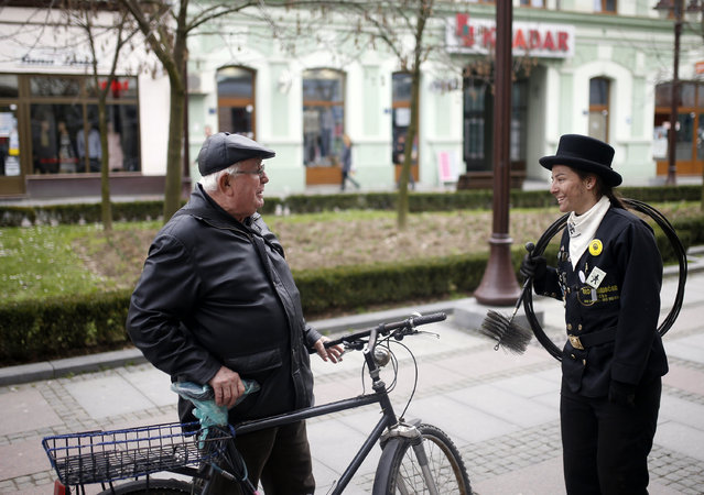 Dajana Djuric, 25, who has worked as a chimney sweep since the age of six, talks to a man after clea
