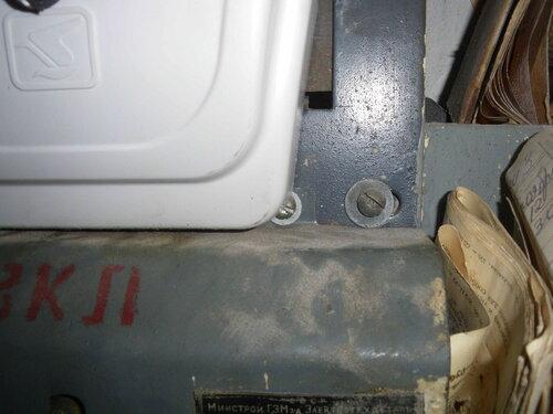 Фото 2. Головка винта, с помощью которого крепится крышка пакетного выключателя, частично накрыта крышкой электросчётчика.