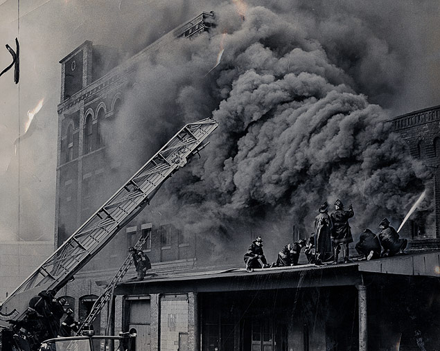 Firemen fight a five-alarm Brooklyn fire from a nearby shed roof