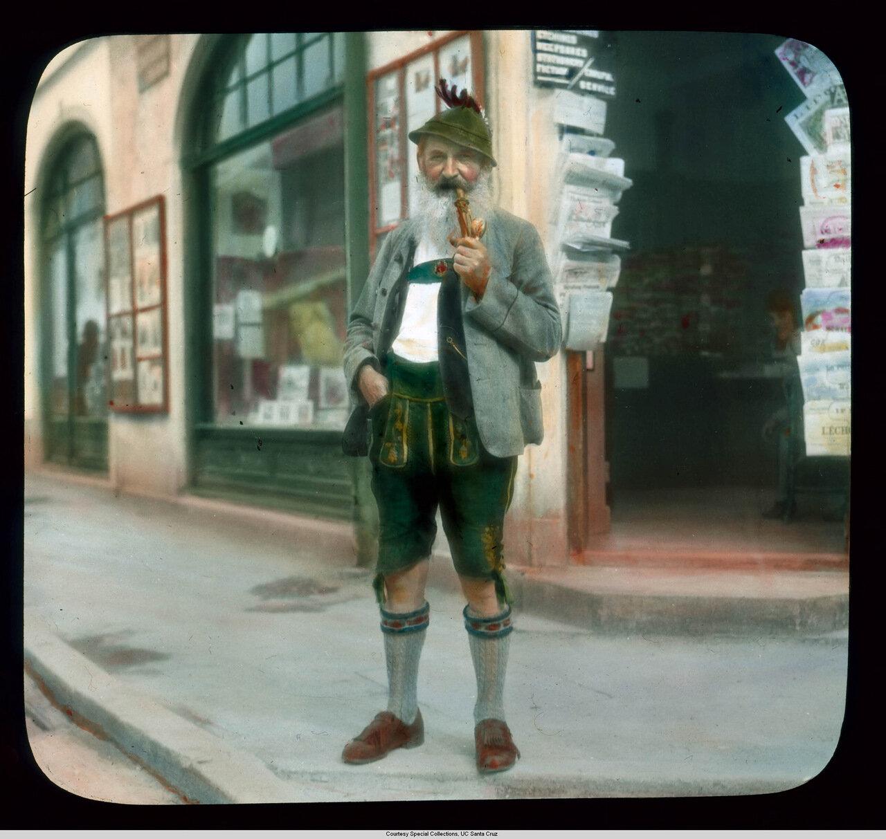 Обераммергау. Страсти Христовы. Баварец в традиционном костюме курит трубку возле Театра Страстей Господних