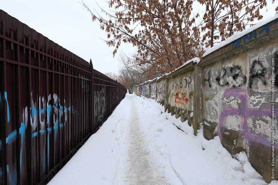 Слева за забором жилой комплекс «Захарково», справа за забором какой-то ангар