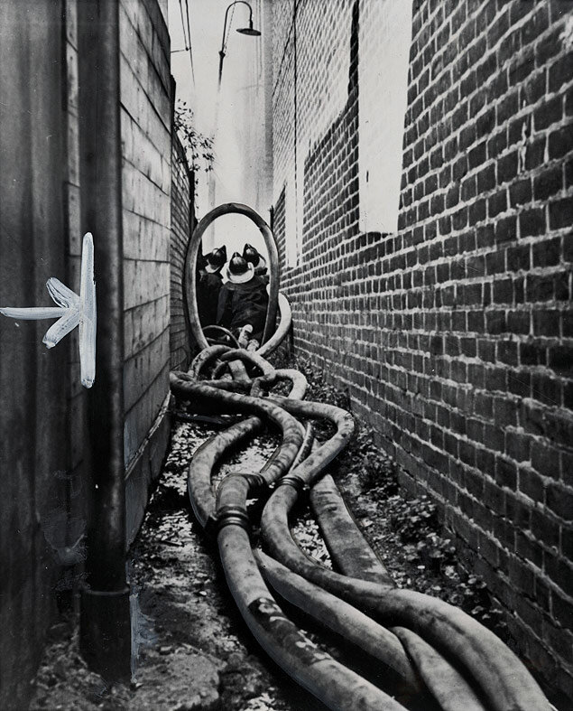 Firemen stretch their hoses through a tight alleyway to fight a warehouse fire in Philadelphia, Pennsylvania