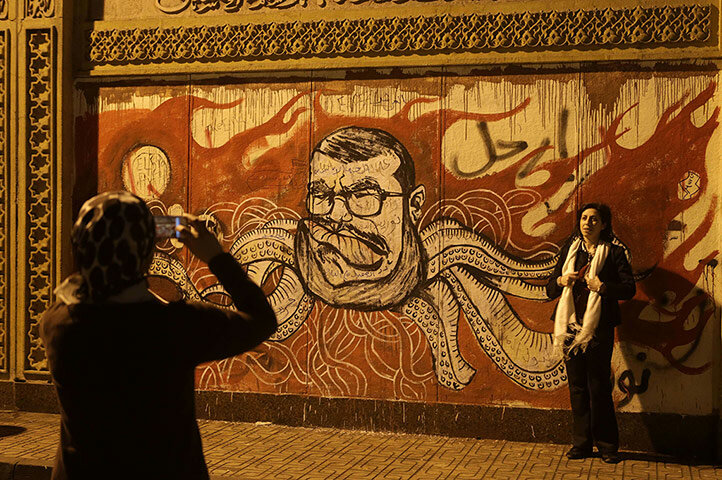 A woman has her photo taken in front of graffiti portraying president Morsi