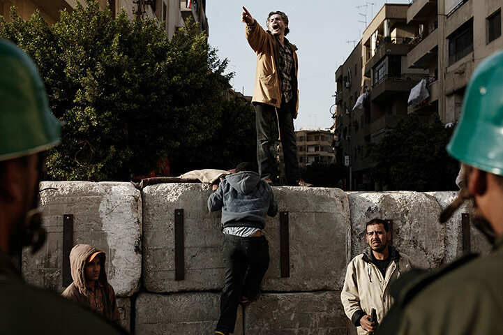 Egyptians climb a concrete wall recently built near the presidential palace
