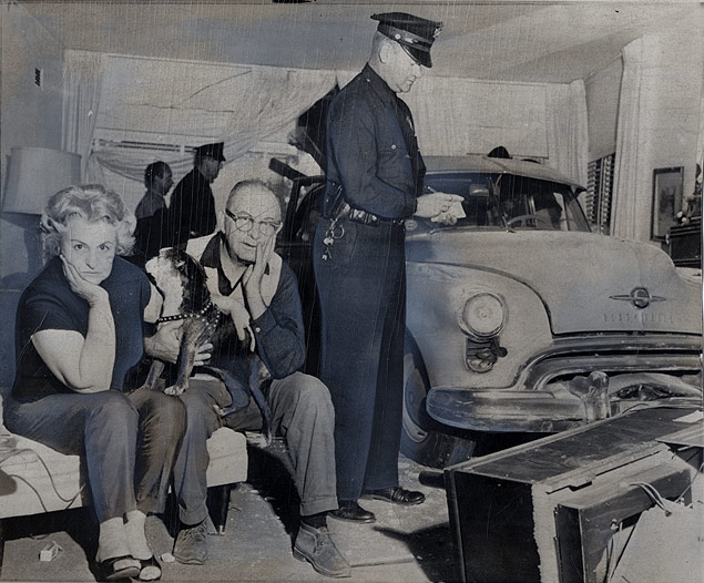 Mr. & Mrs. A.H. Barsha & their dog of Los Angeles, California, look baffled as police view a car which ran out of control and crashed into their living room