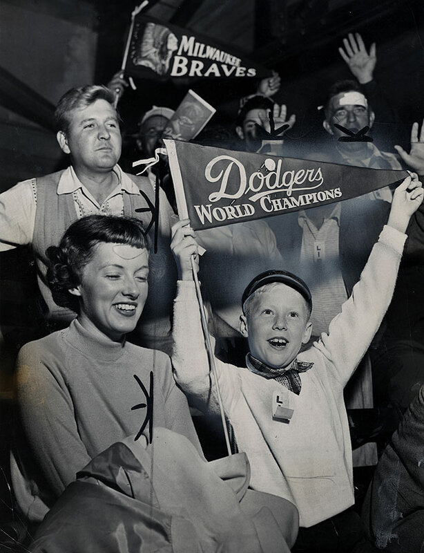 A young Dodgers fan roots for his team as they are victorious against the Milwaukee Braves at Ebbets Field