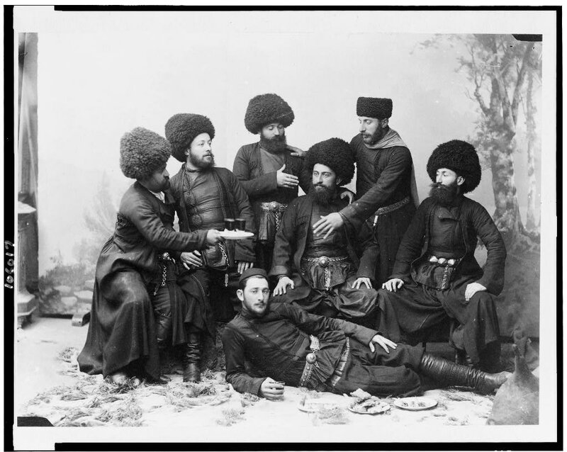 Seven men in Cossak costume, posing as if at a feast, Georgia (Republic).