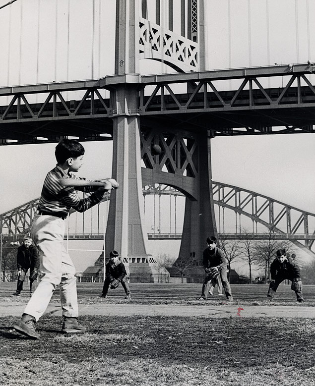 Early spring-like weather brings the boys out to play ball beneath Hell Gate Bridge in Astoria Park, Queens