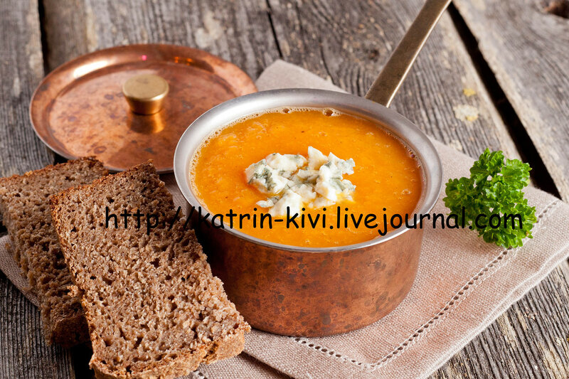 pumpkin soup with blue cheese in a copper pot on a wooden table