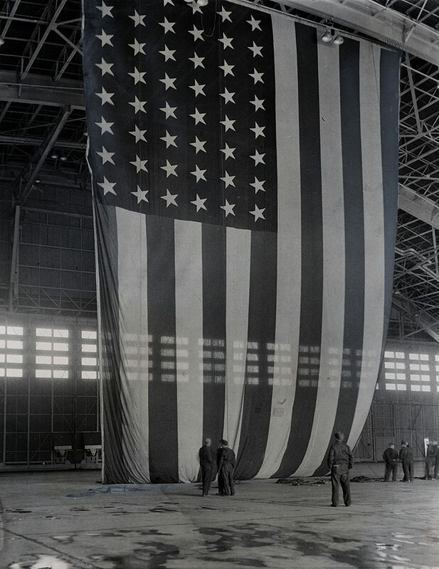 The world's largest free-flying American flag, 90 by 60 feet, is prepared for display at New York International Airport in preparation for the arrival of General Douglas MacArthur