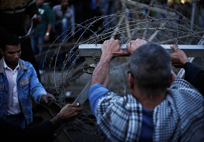 Egyptian protesters take down the barbed wire barrier barricade