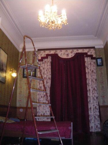 Фото 1. При высоте потолка около четырёх метров для проверки состояния соединения люстры со стационарной проводкой приходится использовать лестницу-стремянку.