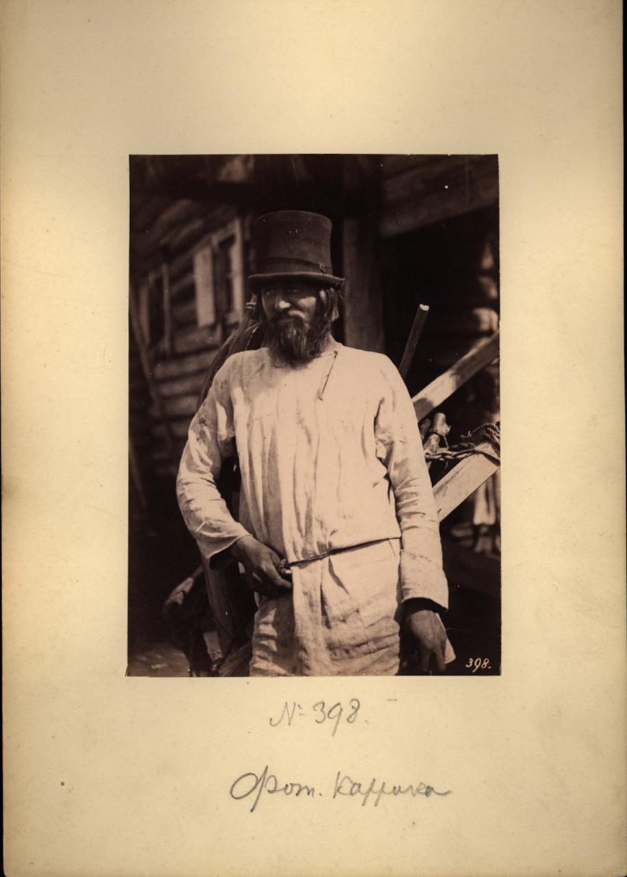 Поволжский крестьянин на фоне избы. 1870-е.