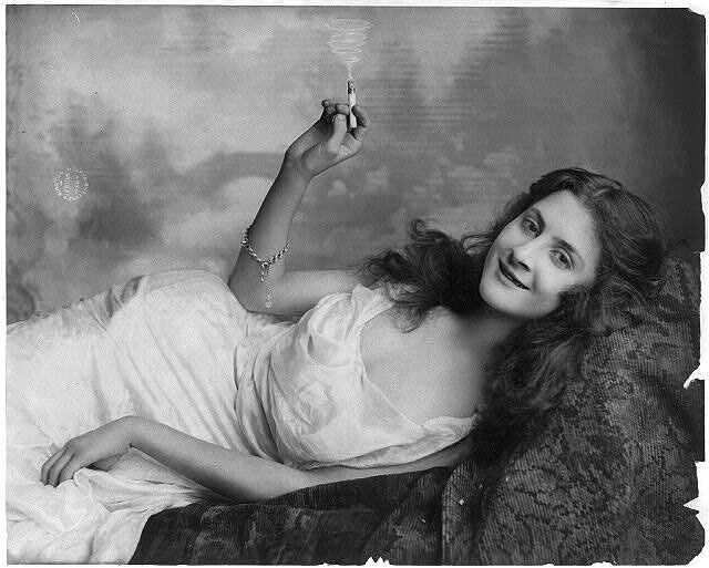 Young woman lying on sofa and holding burning cigarette 1902.