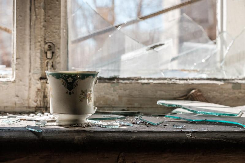 фарфоровая чашка на подоконнике с разбитым стеклом