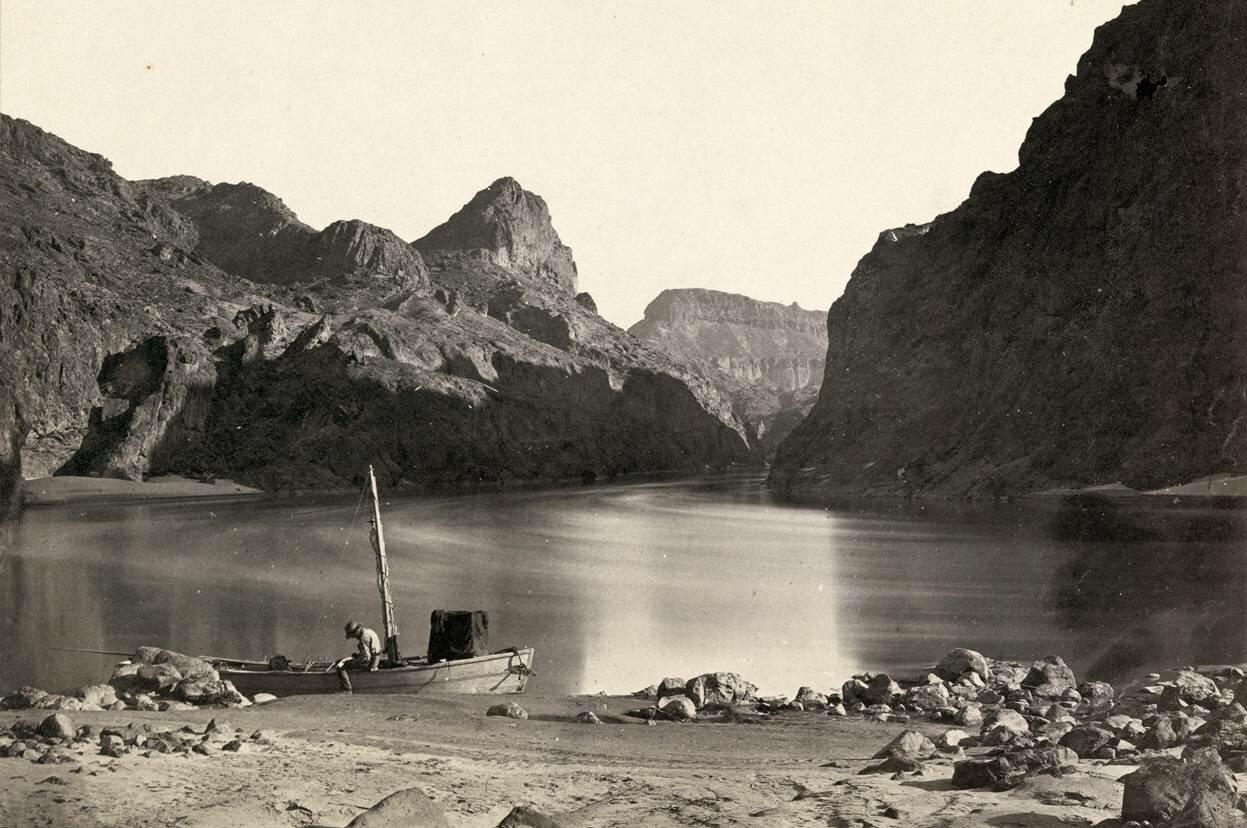 Человек сидит в деревянной лодке у реки Колорадо в Черном Каньоне, Мохаве Каунти, штат Аризона. в 1871 году