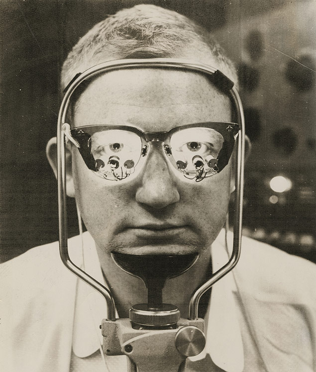 Devereaux Murphy, a research technician at MIT, dons special glasses developed to study eye movements.jpg