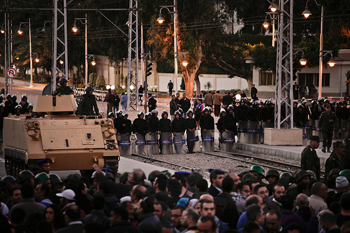 Egyptian riot police stand guard as protesters chant