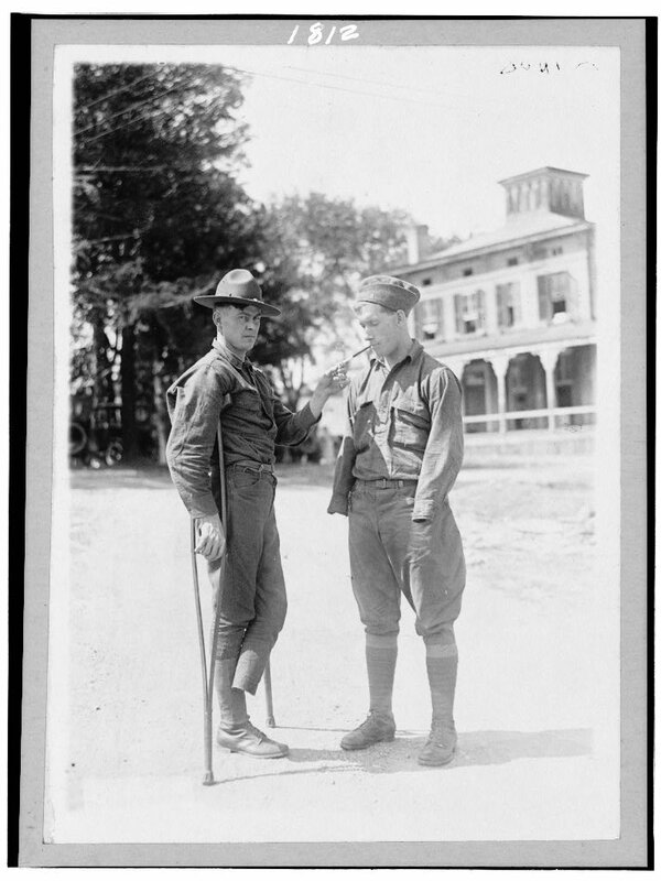 At Walter Reed Hospital, a soldier who is missing a foot lights a cigarette for another soldier who is missing both arms 1918.
