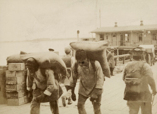 Workers load grain on a boat waiting on the banks of the Volga River, 1918. Photo by William T. Ellis.