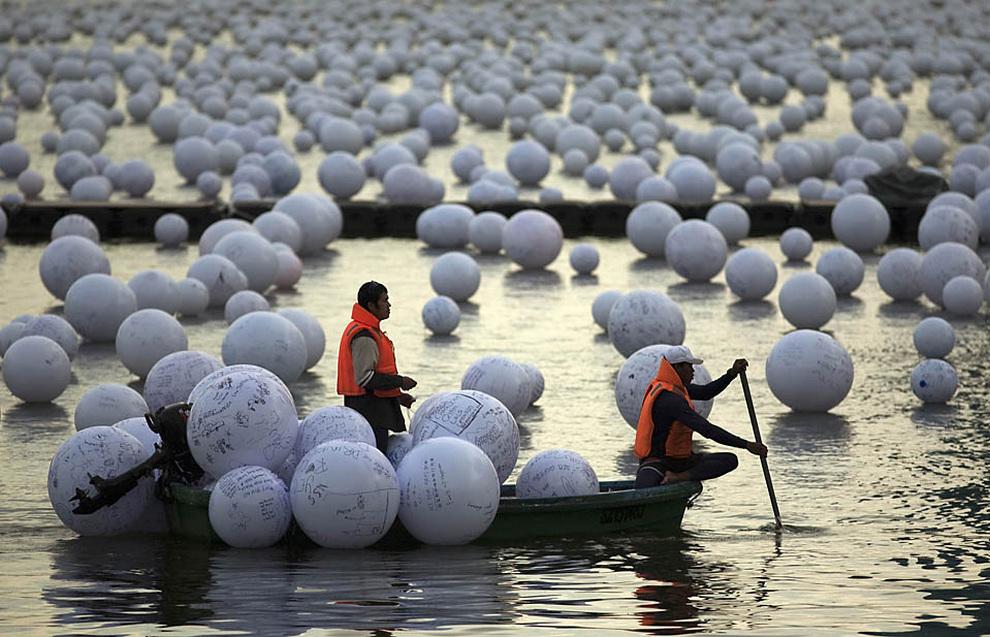 Волонтёры выбрасывают в реку шары с пожеланиями людей, Сингапур
