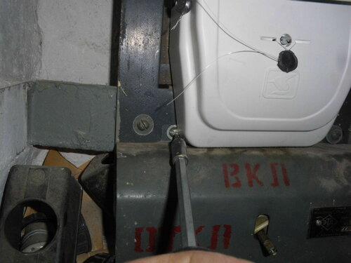 Фото 5. Затягивание винта крепления крышки пакетного выключателя. Из-за несоответствия геометрии квартирного щита и крышки электросчётчика нормальный доступ к головке винта отсутствует, заворачивать винт приходится с осторожностью, чтобы не сорвать шлиц.