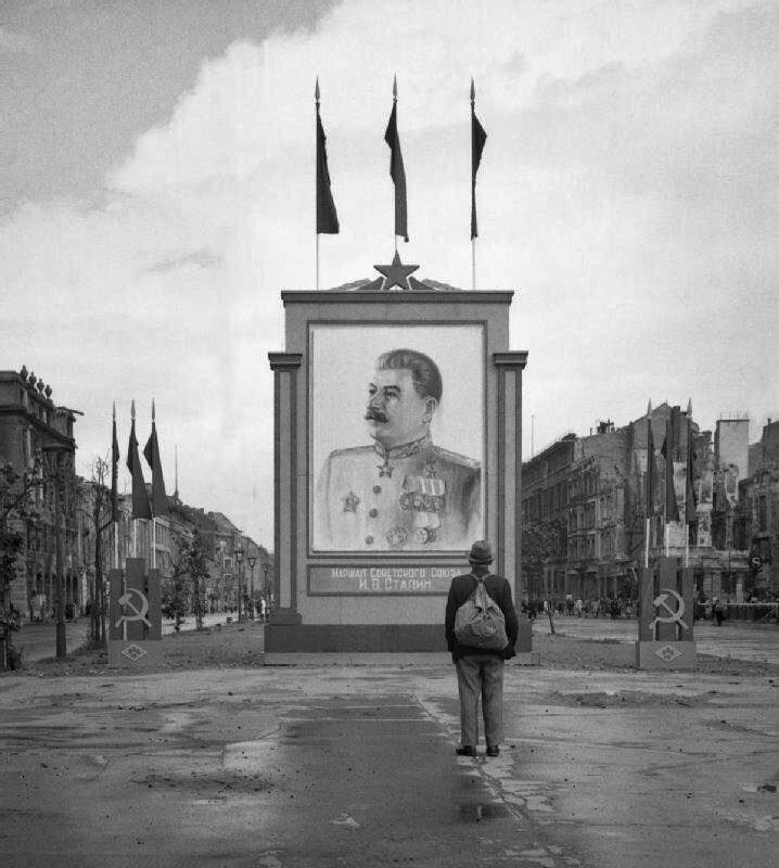 Немец смотрит на плакат со Сталиным на Унтер-ден-Линден в Берлине, 1945 год