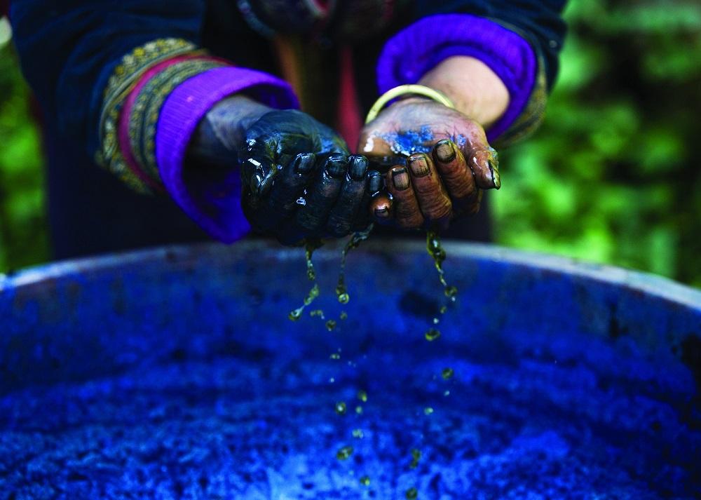 Женские руки в индиго, которым красят одежду. У каждого племени — своя цветная традиционная одежда,