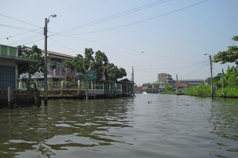 Водный перекрёсток, место слияния двух каналов (клонгов), дорожные указатели, столбы с проводами и дома на воде в Бангкоке, Таиланд