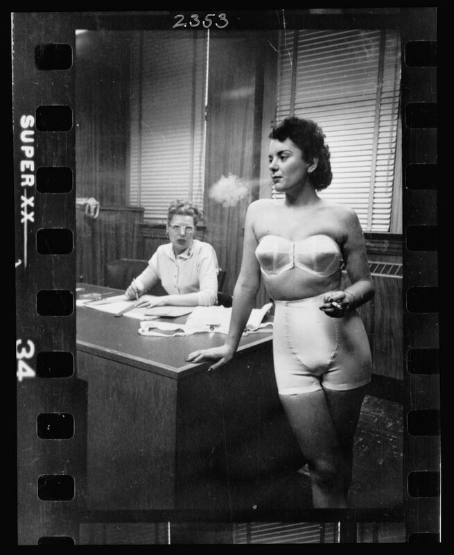 Woman model, standing in an office, smoking while modeling undergarments.
