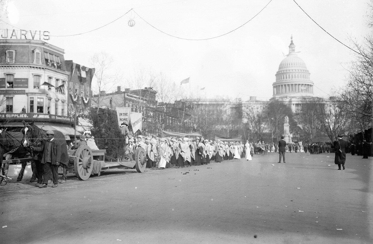 Фрагмент парада. На знаках написано «Дом» и «Домашняя работа», что описывает положение женщин в те годы